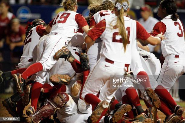 The Crimson Tide dogpile onto Jackie Traina of the University of Alabama after winning the Division I Women's Softball Championship held at ASA Hall...