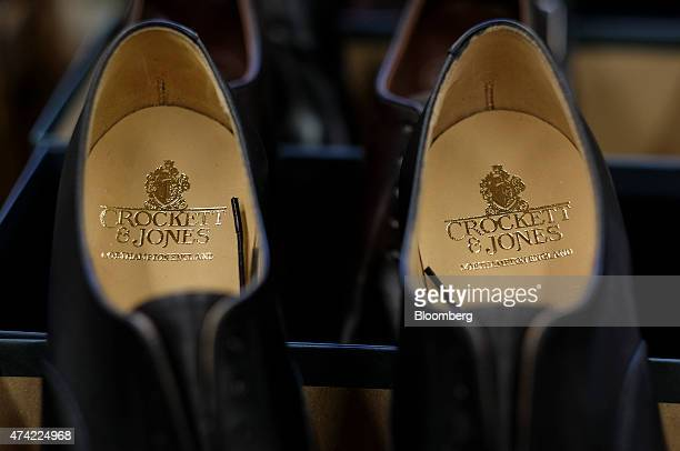 The Crockett Jones logo sits on the insoles of a pair of handmade leather shoes on the finishing line at the Crockett Jones Ltd shoe factory in...