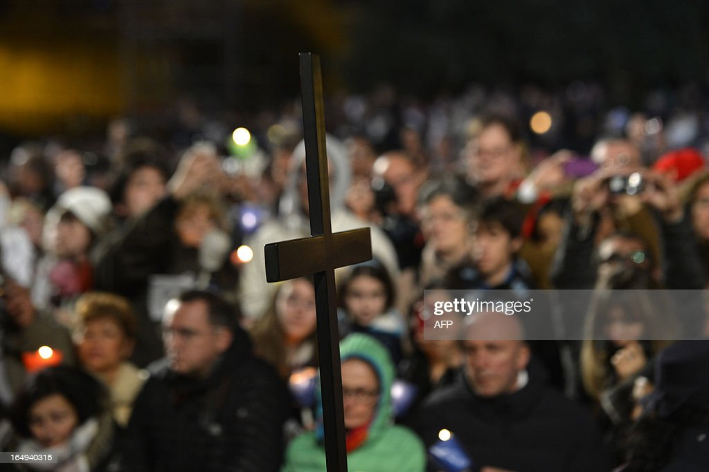 The Cross is carried during the Way of the Cross on Good Friday on March 29, 2013 at the Colosseum in Rome. Pope Francis presided over his first Good Friday which will culminate in a torch-lit procession at Rome's Colosseum and prayers for peace in a Middle East 'torn apart by injustice and conflicts'. AFP PHOTO / ANDREAS SOLARO