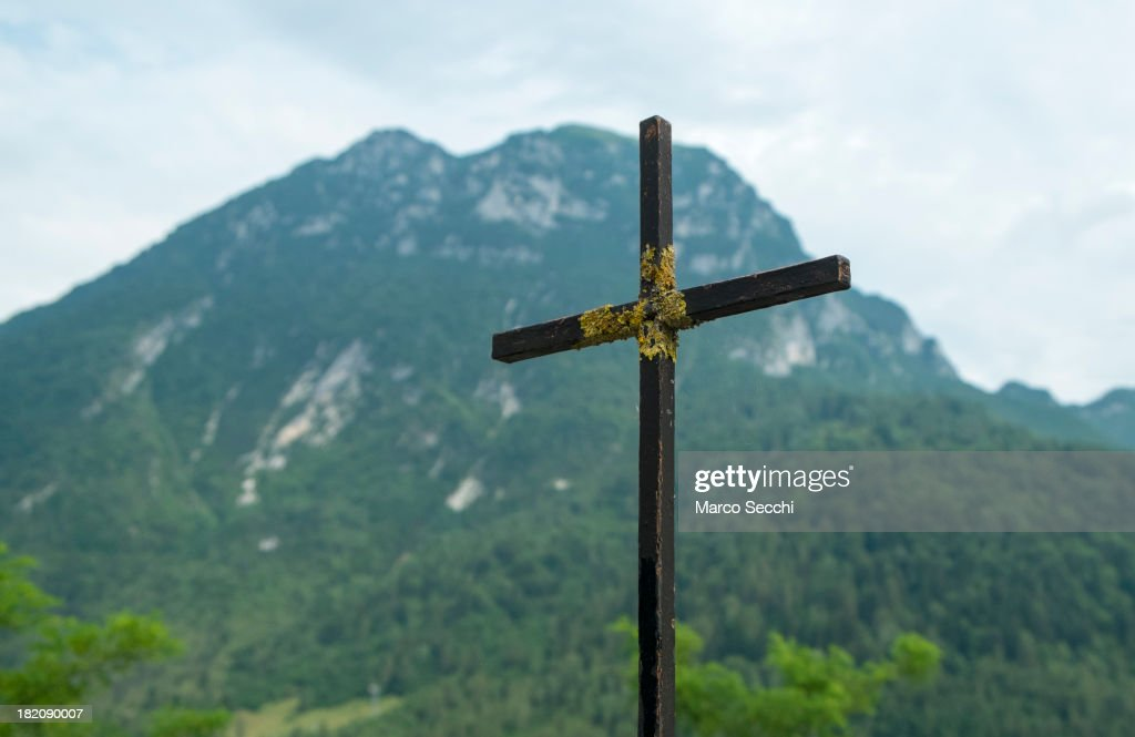 The cross of the cemetery of Ertois seen in front of Mont Toc on September 28, 2013 in Longarone, Italy. The Vajont Dam tragedy happened on the night of the October 9, 1963, when a landslide broke away from Monte Toc and fell into the Vajont River, causing a wave that struck the neighboring towns and killing more than 2000 people.