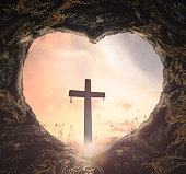 Heart shape of tomb with the cross on meadow sunset background
