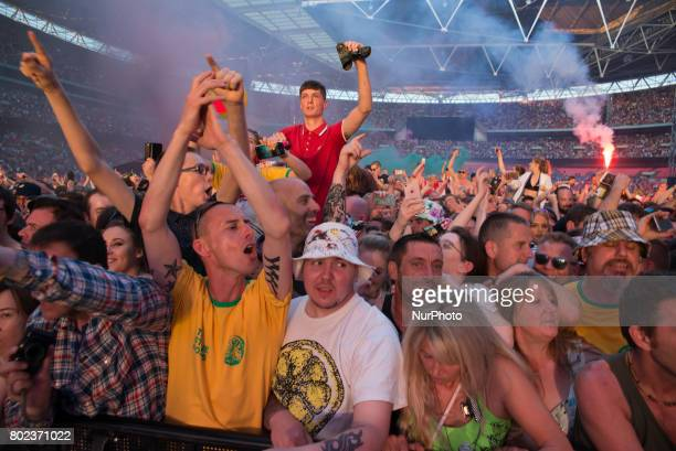 The crowd and stadium smoke are seen at British iconic rock band The Stone Roses's concert at Wembley Stadium London on June 17 2017 The band...