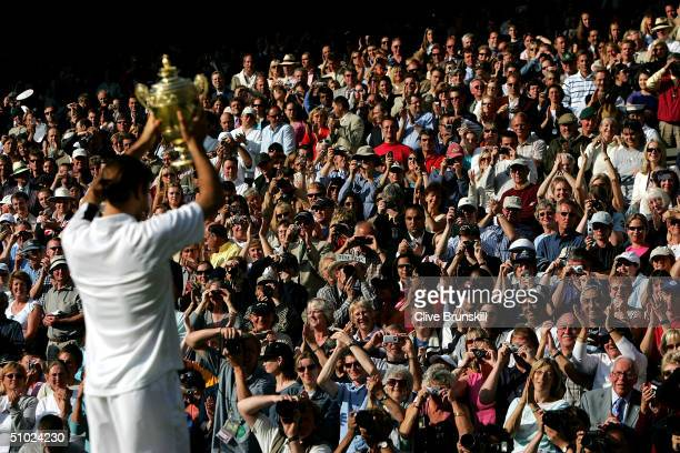 The crowd applauds as Roger Federer of Switzerland lifts his trophy after his victory against Andy Roddick of USA in the men's singles final match...