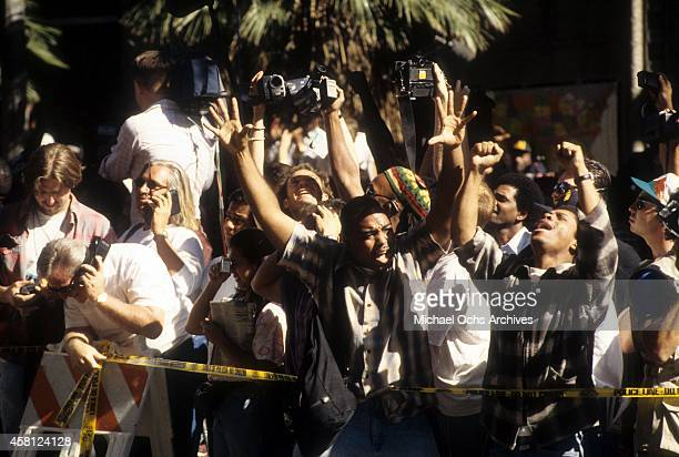 The crowd cheers after hearing the descision of the OJ Simpson verdict at the Los Angeles Courthouse on October 3 1995 in Los Angeles California