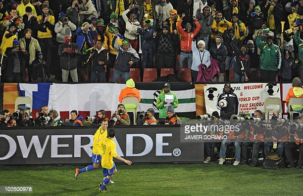 The crowd cheers as Brazil's striker Luis Fabiano celebrates with teammate Kaka after his goal during the 2010 World Cup roundof16 football match...