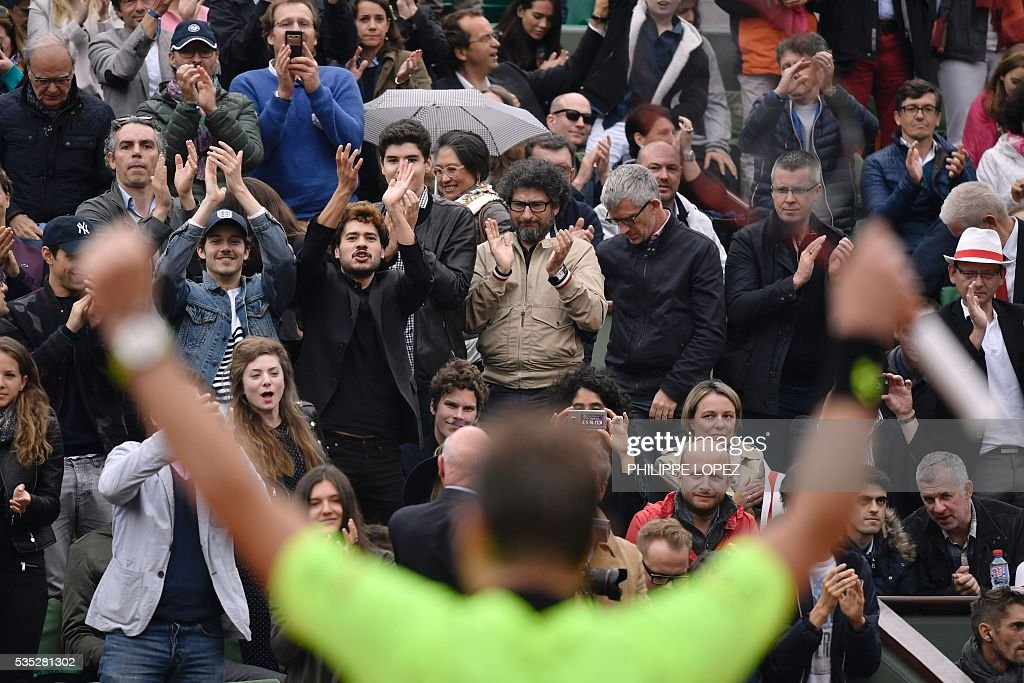The crowd cheers as Switzerland's Stanislas Wawrinka reacts after winning his men's fourth round match against Serbia's Victor Troicki at the Roland Garros 2016 French Tennis Open in Paris on May 29, 2016. / AFP / PHILIPPE