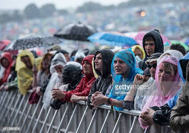 The crowd endure a downpour during the Glastonbury Festival at Worthy Farm on June 28 2014 in Glastonbury England