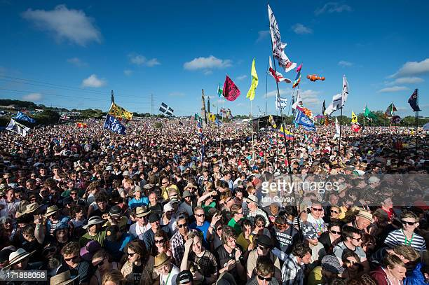 The crowd enjoy the afternoon sunshine before Primal Scream perform on the Pyramid Stage during day 3 of the 2013 Glastonbury Festival at Worthy Farm...
