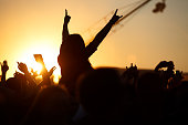The crowd enjoys the summer music festival, sunset, the silhouettes hands up, Silhouette People Party Sunset Celebrate Dancing Concept