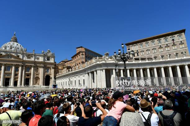 The crowd looks on as Pope Francis addresses them from the window of the apostolic palace overlooking St Peter's Square during his Angelus prayer at...