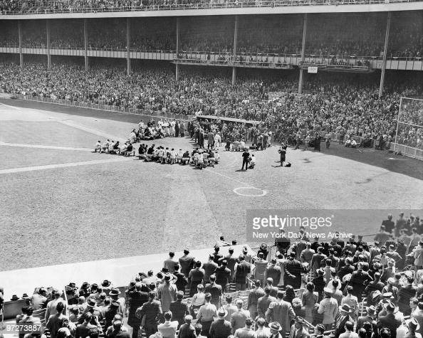 The crowd rises and roars as Babe Ruth steps to microphone near Yankee dugout Players crouch around him as he thanks everyone for everything