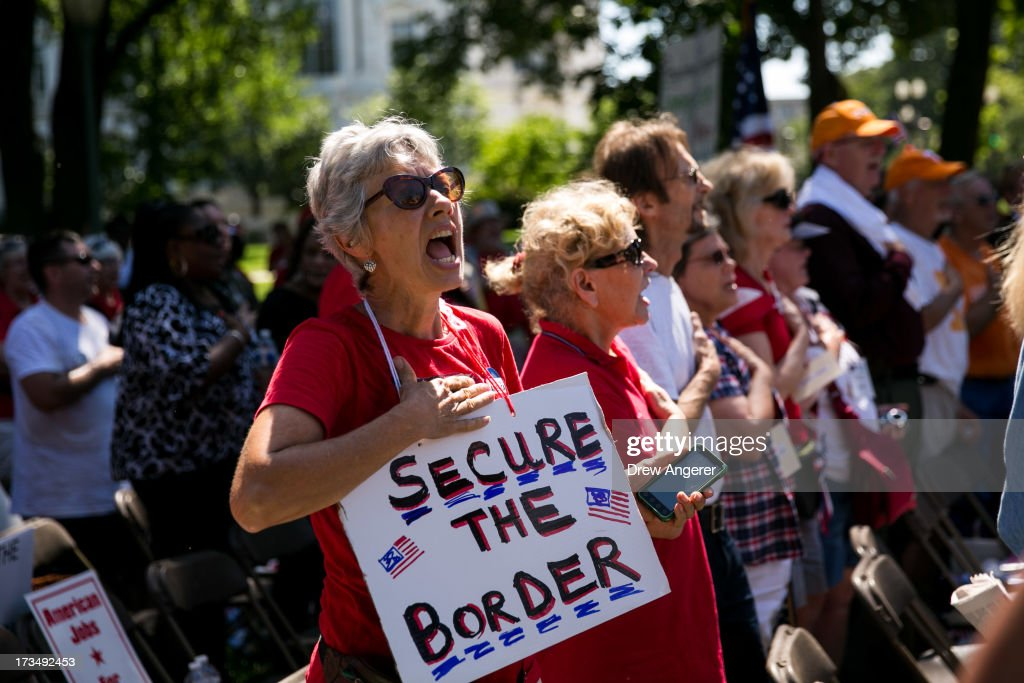 The crowd sings the National Anthem during the DC March for Jobs in Upper Senate Park near Capitol Hill, on July 15, 2013 in Washington, DC. Conservative activists and supporters rallied against the Senate's immigration legislation and the impact illegal immigration has on reduced wages and employment opportunities for some Americans.