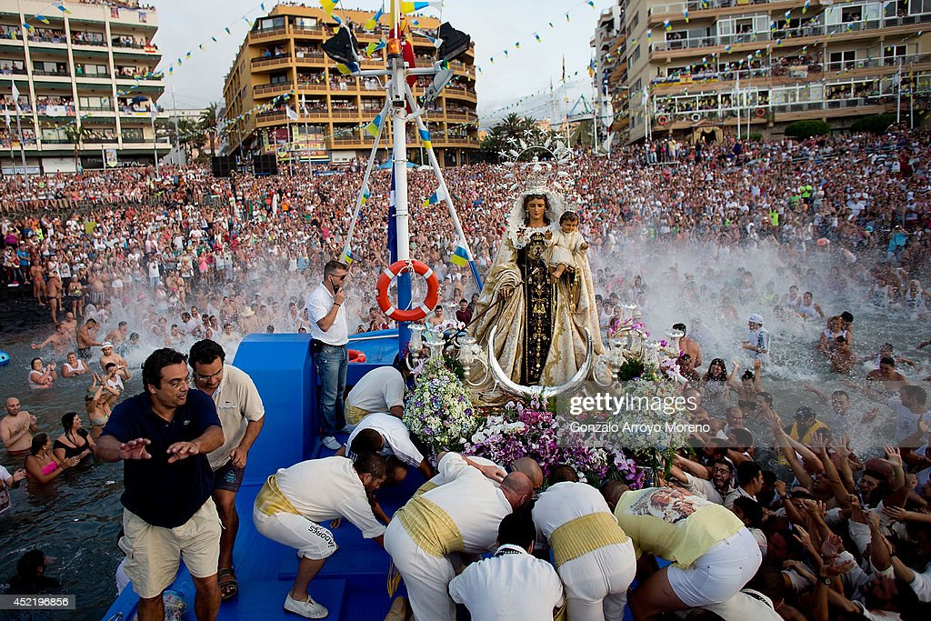 The crowd touch the Virgen del Carmen statue loaded at New Saint Ramon boat for its journey on July 15, 2014 at Puerto de la Cruz dock on the Canary island of Tenerife, Spain. Since 1921, the statue of the Virgen del Carmen, patron saint of fishermen, has been carried with great fanfare annually as part of July Festivities to the Puerto de la Cruz dock where, at the end of its procession, it is hoisted aboard a decorated boat. Weather permitting, the boat carrying the statue, accompanied by a flotilla of other boats, makes a short journey along the island coast before returning to the harbour. In recent years, attendance at the event has numbered more than 35,000 people.