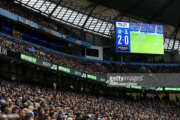 The crowd watch as the big screen shows the action during the Barclays Premier League match between Manchester City and Crystal Palace at the Etihad...