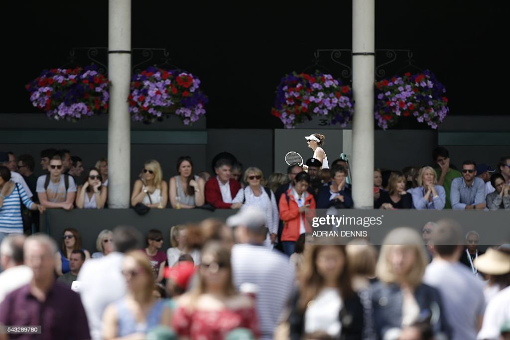 The crowd watch play as Australia's Samantha Stosur is seen against Poland's Magda Linette on the next court during their women's singles first round match on the first day of the 2016 Wimbledon Championships at The All England Lawn Tennis Club in Wimbledon, southwest London, on June 27, 2016. / AFP / ADRIAN