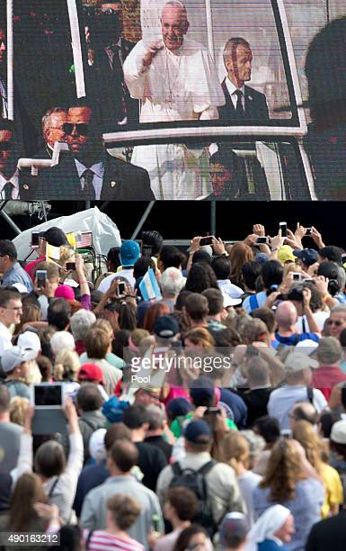 The crowd watches on a giant television as Pope Francis greets the crowd from the Pope Mobile as he arrives at Independence Mall on September 26 2015...