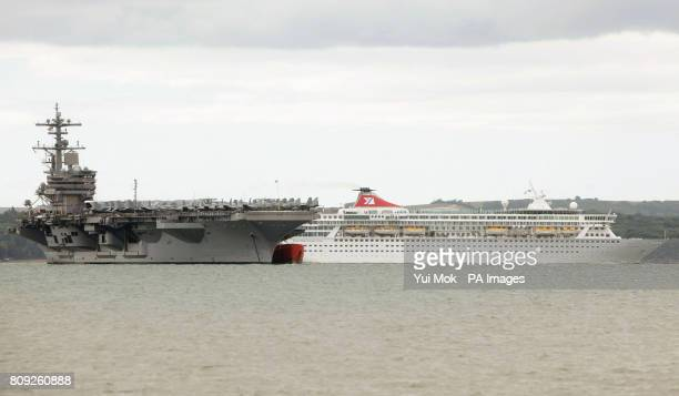 The cruise ship Balmoral passes the United States Navy Nimitzclass supercarrier the USS George HW Bush in Stokes Bay off the coast of Portsmouth