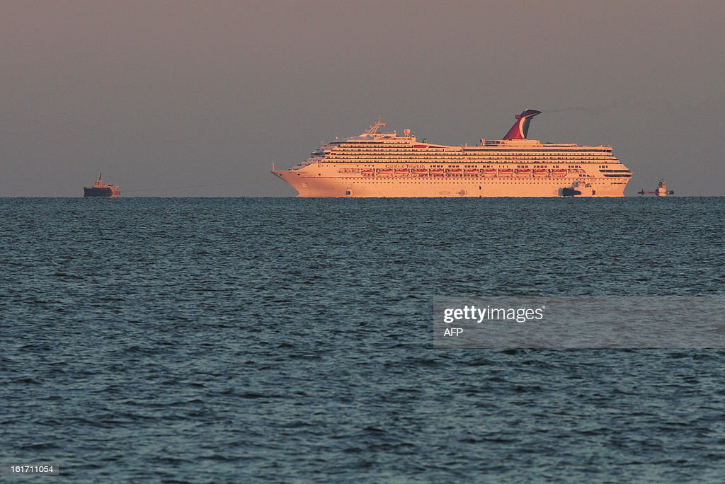 The cruise ship Carnival Triumph makes its way up Mobile Bay assisted by tug boats near Dauphin Island, Alabama, February 14, 2013. Passengers on a stricken cruise ship in the Gulf of Mexico are enduring a nightmare after days without power, waiting hours for sparse meals and relieving themselves in plastic bags, one said February 14, 2013. The ship Triumph, owned by Carnival, suffered an engine room fire Sunday, February 11, 2013, that left it disabled and adrift as it carried more than 4,000 people. It is being towed to Mobile, Alabama and was to arrive Thursday afternoon, February 14, 2013. Meanwhile, the sunny and pleasant cruise people paid for has turned in a gruesome, smelly ordeal. AFP PHOTO / Dan ANDERSON