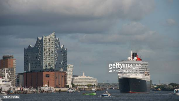 The cruise ship 'Queen Mary 2' passing the Elbe Philharmonic Hall in the port of Hamburg on August 21 2017 / AFP PHOTO / dpa / Daniel Reinhardt /...
