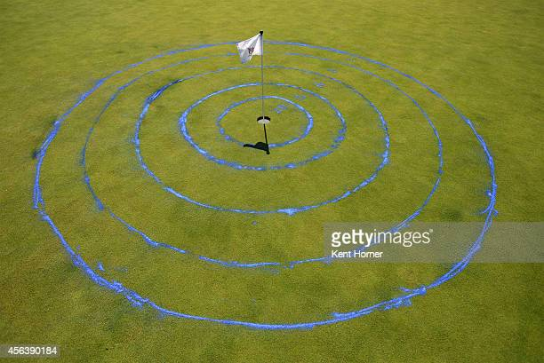 The cup flag stick shows the center of the scoring rings surrounding a hole in the putting competition during a regional round of the Drive Chip and...