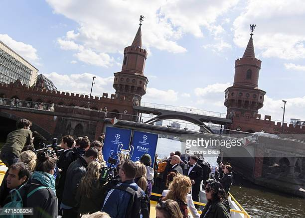 The cup is pictured between journalists on a boat on the river Spree in front of the Oberbaumbruecke during the UEFA Champions League Trophy Tour...