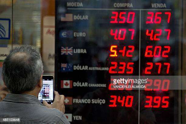 The currencies board of a bureau of change in Rio de Janeiro Brazil shows on August 24 2015 an exchange rate of 255 reals per US dollar Stocks in...