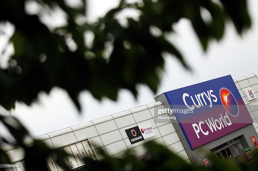 The Currys and PC World logos are displayed above the entrance of a Currys and PC World 2 in 1 store, operated by Dixons Retail Plc, in Manchester, U.K., on Tuesday, June 18, 2013. Dixons Retail Plc, the U.K.'s largest consumer-electronics retailer, said last month it will report annual pretax profit at the 'top end' of analysts' predictions after fourth-quarter revenue beat estimates on increased sales of tablets and services such as software tutorials. Photographer: Paul Thomas/Bloomberg via Getty Images