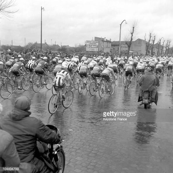 The cyclists on the wet pavements of a street in SaintDenis suburbs a short time after the start of ParisRoubaix race