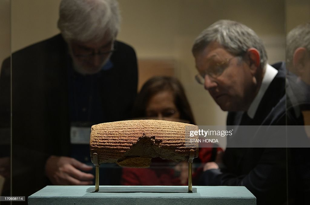 The Cyrus Cylinder, Achaemenid, 539-538 B.C., excavated at Babylon, Iraq, 1879, on display in 'The Cyrus Cylinder and Ancient Persia: Charting a New Empire' and viewed by Ira Spar (L), of The Metropolitan Museum of Art's Department of Ancient Near Eastern Art, Joan Aruz (C, partly hidden), Curator in Charge, Department of Ancient Near Eastern Art and John Curtis (R), Keeper of Special Middle East Projects, British Museum, June 20, 2013 at The Metropolitan Museum of Art in New York. The Cyrus Cylinder is a 2,600-year-old inscribed clay document from Babylon in ancient Iraq and one of the most famous surviving icons from the ancient world is part of a traveling exhibition organized by the British Museum. The Cylinder marks the establishment of Persian rule in 539 B.C. by Cyrus the Great, with the defeat of Babylon, the restoration of shrines, and the return of deported peoples and their gods. The Cyrus Cylinder and 16 related works on view, all on loan from the British Museum, reflect the innovations initiated by Persian rule in the ancient Near East (550331 B.C.) and chart a new path for this empire, the largest the world had known. AFP PHOTO/Stan HONDA