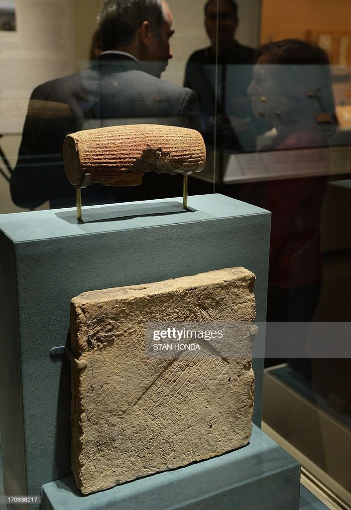 The Cyrus Cylinder (top), Achaemenid, 539-538 B.C., excavated at Babylon, Iraq, 1879, on display with a fragment of tablet with Babylonian cuneiform inscription (bottom), Achaemenid, 539-538 B.C., excavated at Babylon, Dilbat or Borsippa, Iraq, 1880-81 in 'The Cyrus Cylinder and Ancient Persia: Charting a New Empire' June 20, 2013 at The Metropolitan Museum of Art in New York. The Cyrus Cylinder is a 2,600-year-old inscribed clay document from Babylon in ancient Iraq and one of the most famous surviving icons from the ancient world is part of a traveling exhibition organized by the British Museum. The Cylinder marks the establishment of Persian rule in 539 B.C. by Cyrus the Great, with the defeat of Babylon, the restoration of shrines, and the return of deported peoples and their gods. The Cyrus Cylinder and 16 related works on view, all on loan from the British Museum, reflect the innovations initiated by Persian rule in the ancient Near East (550331 B.C.) and chart a new path for this empire, the largest the world had known. AFP PHOTO/Stan HONDA