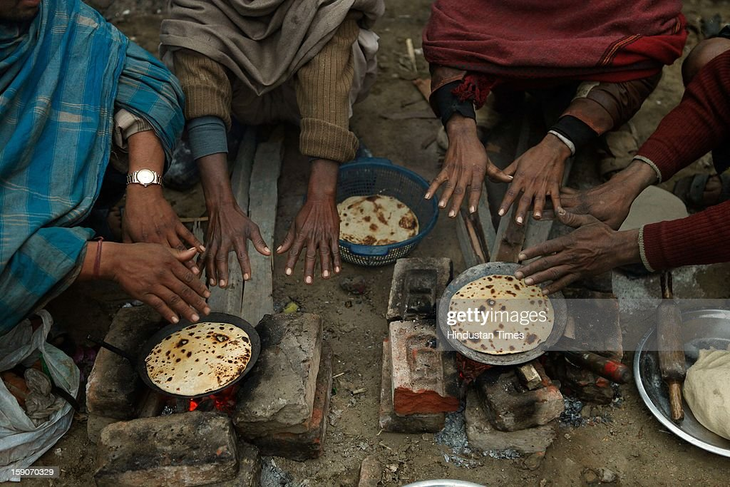 The daily wage labours cook the meal and sit near the fire on the foggy and cold morning near Patpar Ganj on January 7, 2013 in New Delhi, India. Dense fog and icy winds disrupted normal life as Delhi's minimum temperature settled at five notches below average at 2.4 degrees Celsius. Fog forced visibility to drop to about 500 metres in the morning resulting in 15 flights and 42 trains were delayed out of Delhi while 18 trains got cancelled.