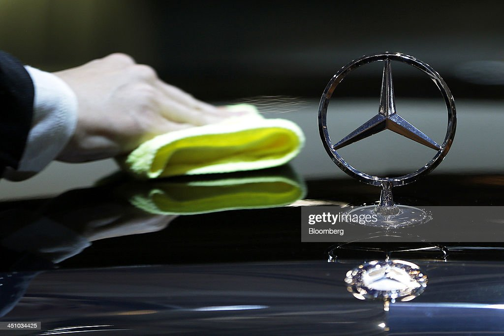 The Daimler AG Mercedes-Benz emblem sits on the hood of the S 65 AMG long vehicle as an attendant wipes down the vehicle at the 43rd Tokyo Motor Show 2013 in Tokyo, Japan, on Thursday, Nov. 21, 2013. The autoshow will be open to the public from Nov. 23 to Dec. 1 at the Tokyo International Exhibition Center, also known as the Tokyo Big Sight. Photographer: Kiyoshi Ota/Bloomberg via Getty Images