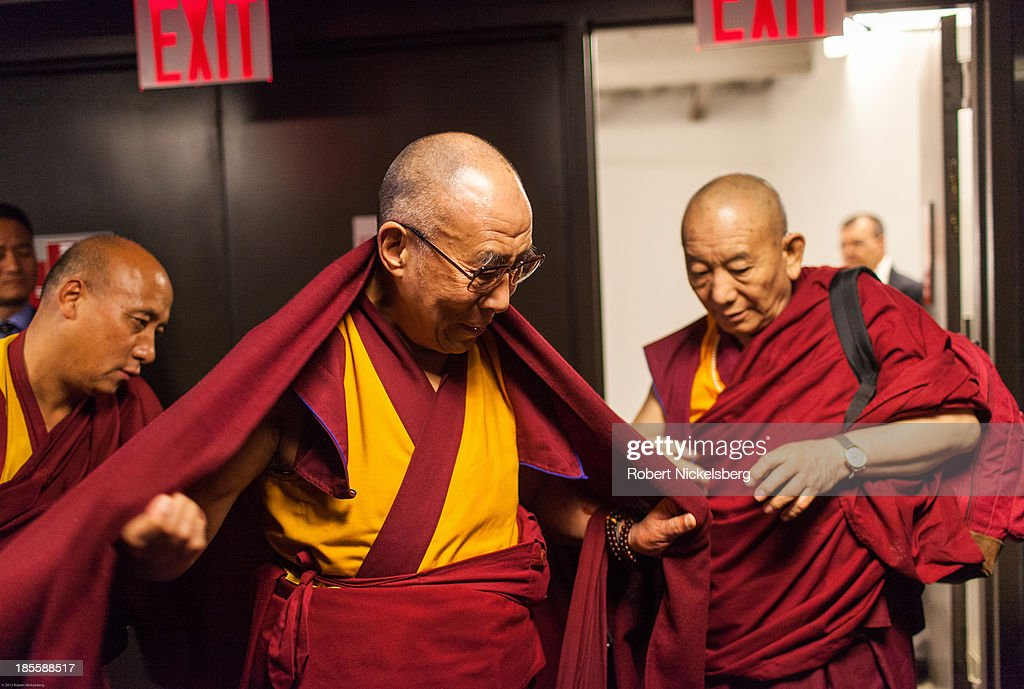 The Dalai Lama adjusts his shawls before being escorted to his plane leaving for Germany October 21, 2013 at JFK Airport in New York City. The Dalai Lama was in New York City for three days of his Buddhist teachings that ran October 18-20.