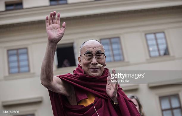 The Dalai Lama gestures as he attends a gathering with his supporters at the Hradcanske Square in front of Prague Castle on October 17 2016 in Prague...