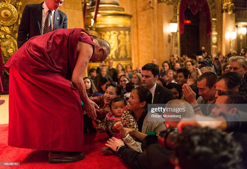 The Dalai Lama greets an audience at the Beacon Theater October 20, 2013 in New York City. The Dalai Lama is in New York City for three days of his Buddhist teachings that run October 18-20. The teachings are supported by the Richard Gere Foundation.