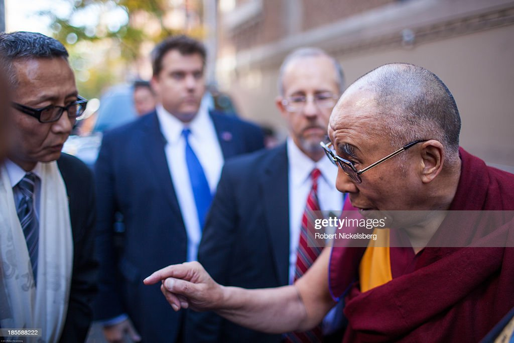 The Dalai Lama (R) instructs a staff member before leaving the Beacon Theater October 21, 2013 in New York City. The Dalai Lama was in New York City for three days of his Buddhist teachings that ran October 18-20 and were supported by the Richard Gere Foundation.