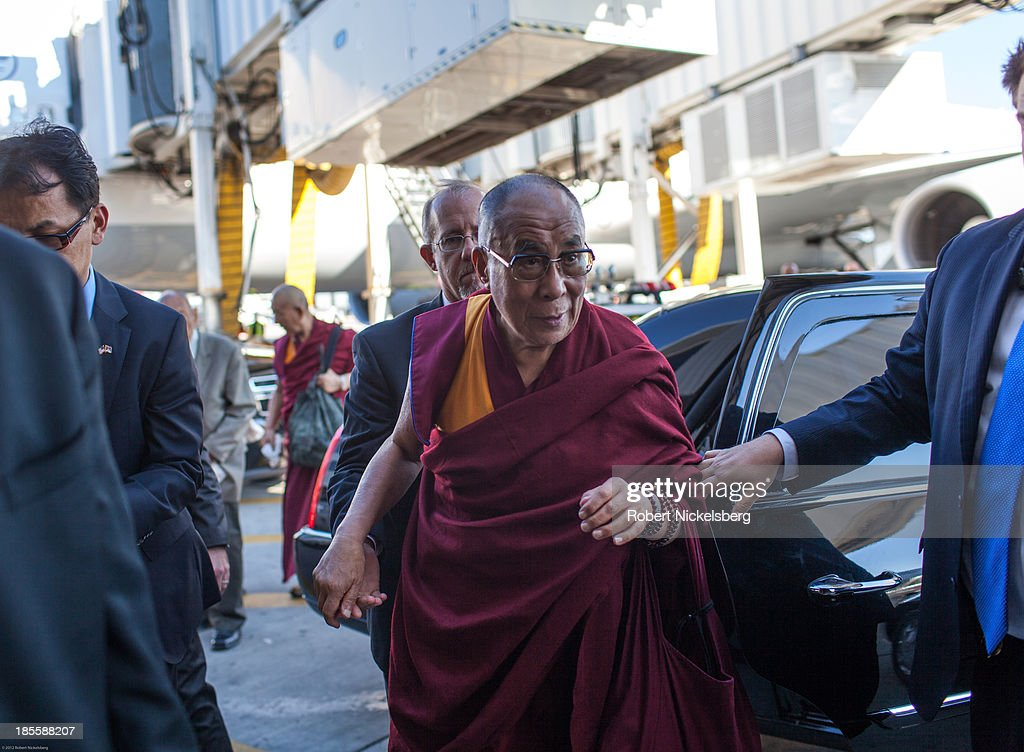 The Dalai Lama is escorted to his plane by U.S. Department of State diplomatic security before leaving for Germany October 21, 2013 in the Queens borough of New York City. The Dalai Lama was in New York City for three days of his Buddhist teachings that ran October 18-20 and were supported by the Richard Gere Foundation.