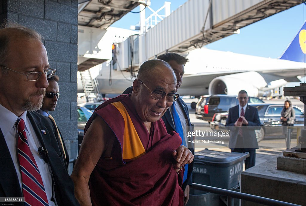 The Dalai Lama is escorted to his plane by U.S. Department of State diplomatic security before leaving for Germany October 21, 2013 at JFK Airport in New York City. The Dalai Lama was in New York City for three days of his Buddhist teachings that ran October 18-20.