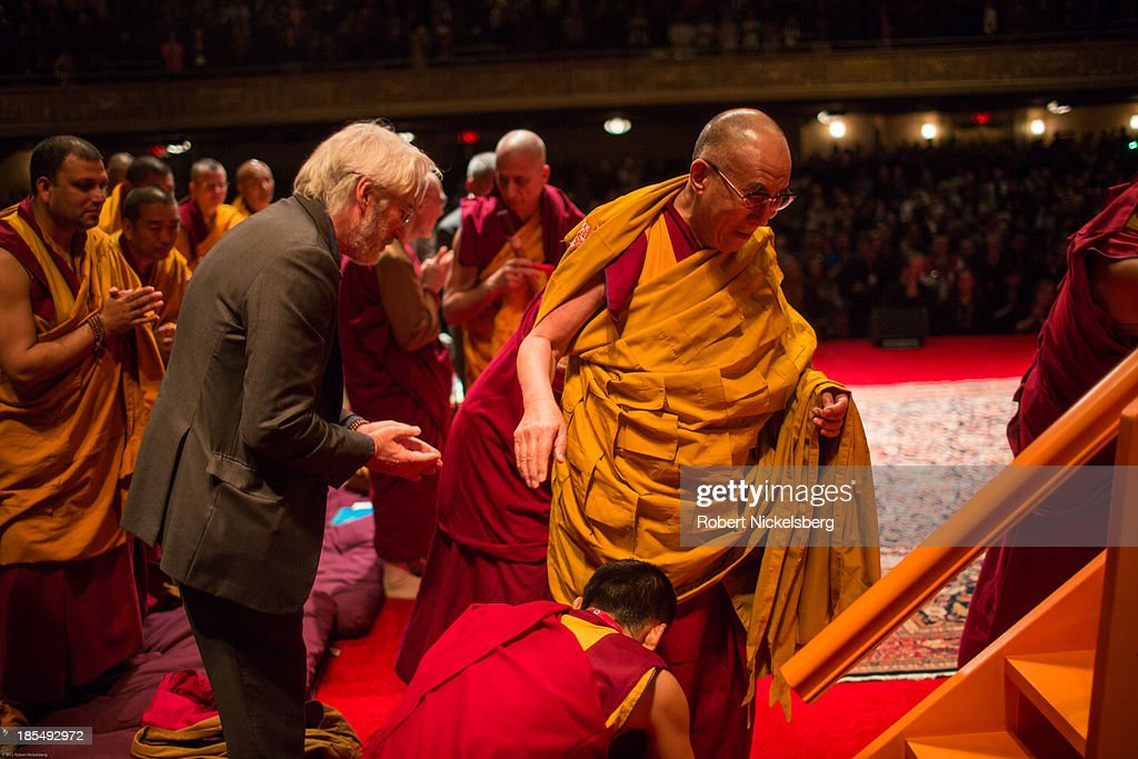 The Dalai Lama is helped to his speaking platform by actor Richard Gere, (L)and a monk during an initiation ceremony at the Beacon Theater October 20, 2013 in New York City. The Dalai Lama is in New York City for three days of his Buddhist teachings that run October 18-20. The teachings are supported by the Richard Gere Foundation.