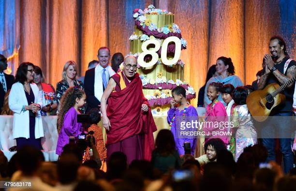 The Dalai Lama reacts as his birthday caked is wheeled out on stage following a performance for him by children at the Honda Center in Anaheim...