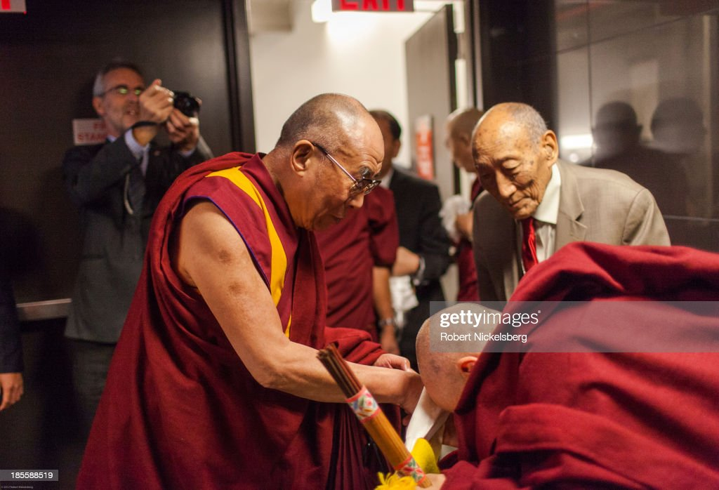 The Dalai Lama says goodbye to Buddhist monk Nicholas Vreeland (2nd R) and Khyongla Rato Rinpoche, (R) before leaving for Germany October 21, 2013 at JFK Airport in New York City. The Dalai Lama was in New York City for three days of his Buddhist teachings that ran October 18-20.