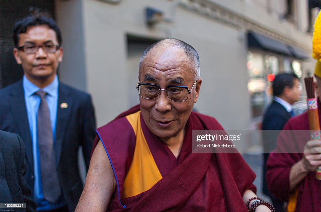 The Dalai Lama (C) says goodbye to followers outside the Beacon Theater October 21, 2013 in New York City. The Dalai Lama was in New York City for three days of his Buddhist teachings that ran October 18-20 and were supported by the Richard Gere Foundation.