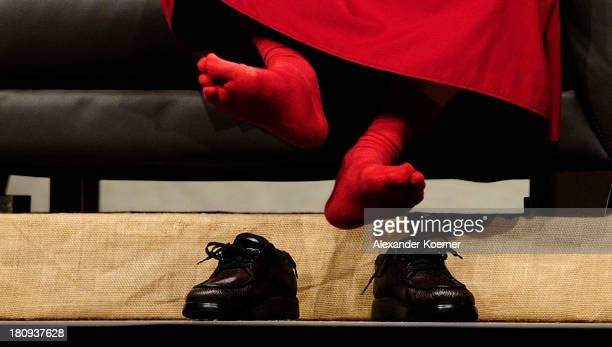 The Dalai Lama unties his shoes during a speech on 'Strength Through Compassion and Tolerance' at the Swiss Life Hall on September 18 2013 in Hanover...