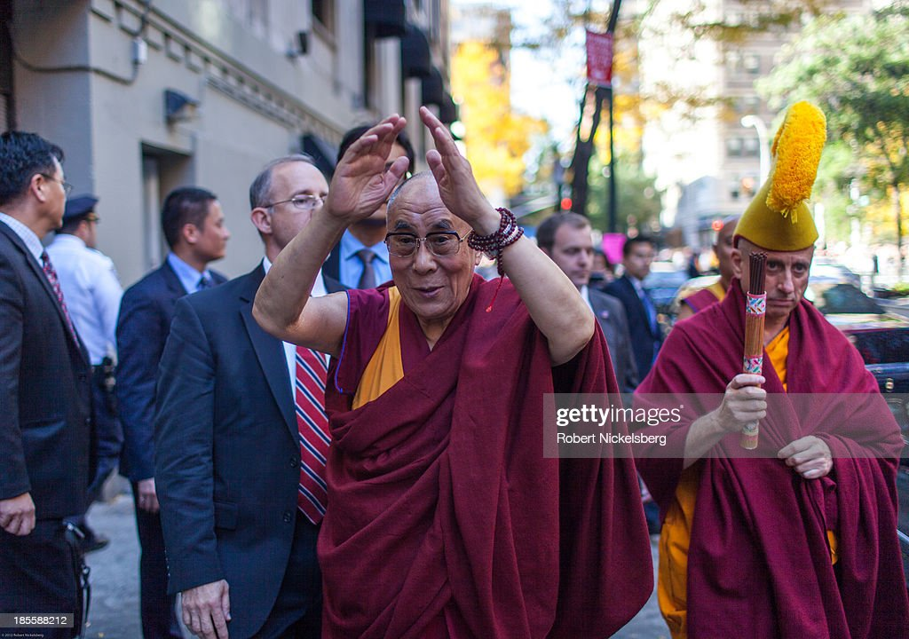 The Dalai Lama (3rd R) waves goodbye to followers outside the Beacon Theater October 21, 2013 in New York City. The Dalai Lama was in New York City for three days of his Buddhist teachings that ran October 18-20 and were supported by the Richard Gere Foundation.