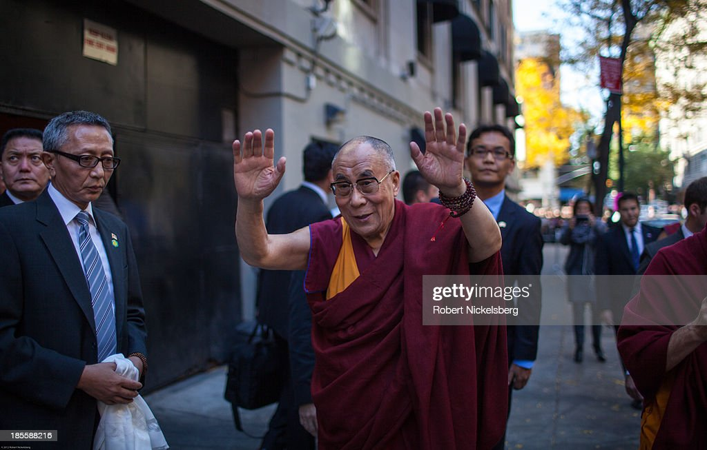 The Dalai Lama (3rd L) waves goodbye to followers outside the Beacon Theater October 21, 2013 in New York City. The Dalai Lama was in New York City for three days of his Buddhist teachings that ran October 18-20 and were supported by the Richard Gere Foundation.