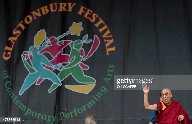 The Dalai Lama waves to the crowd from the Pyramid Stage as he visits the Glastonbury Festival of Music and Performing Arts on Worthy Farm near the...