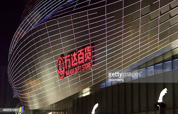 The Dalian Wanda Group Co logo is displayed outside the Tongzhou Wanda Plaza shopping mall at night in Beijing China on Saturday March 14 2015 Dalian...
