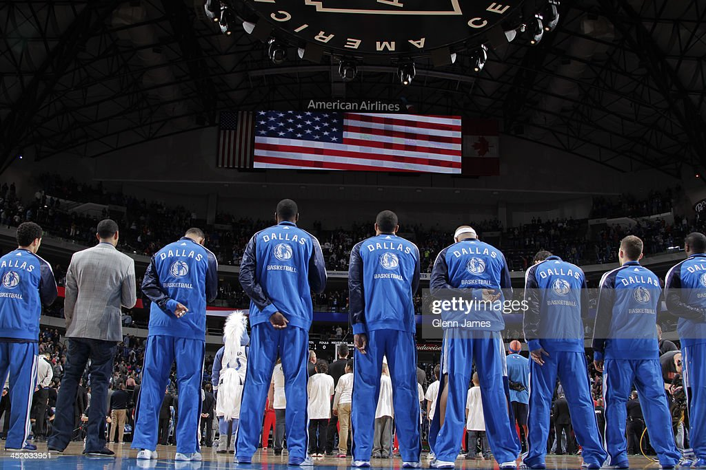 The Dallas Mavericks stand on the court against the Houston Rockets on November 20, 2013 at the American Airlines Center in Dallas, Texas.