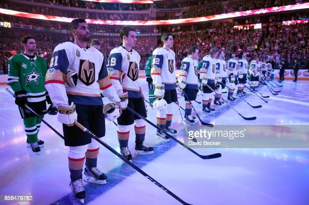 The Dallas Stars stand behind the Vegas Golden Knights during a moment of silence before the season opening game at American Airlines Center on...