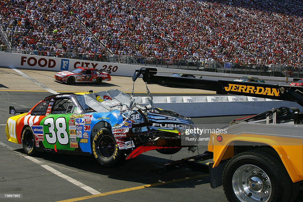 The damaged car of David Gilliland driver of the MM's Ford is towed behind the wall after crashing during the NASCAR Nextel Cup Series Food City 500...
